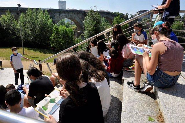 Un grupo de alumnos de un colegio dibuja cerca del Puente Romano,en Ourense.