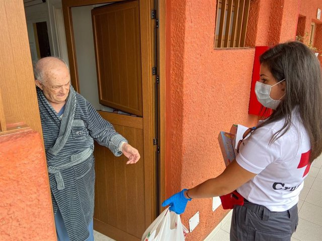 Archivo - Una voluntaria de Cruz Roja presta ayuda a una persona mayor durante el estado de alarma