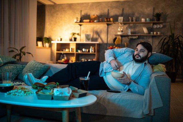 Archivo - Hombre tumbado en el sofá. Sedentarismo.