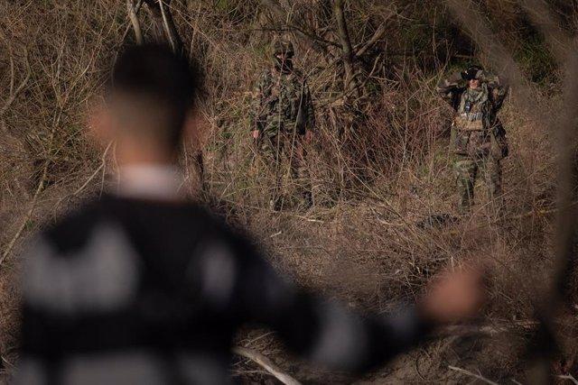 Archivo - Un migrante observa desde la costa turca mientras los soldados griegos patrullan el borde del río Evros el 3 de marzo de 2020 en Edirne, Turquía.