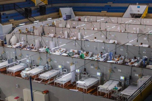 Archivo - Personas afectadas por coronavirus reciben tratamiento en un hospital de campaña construido dentro de una pista cubierta.