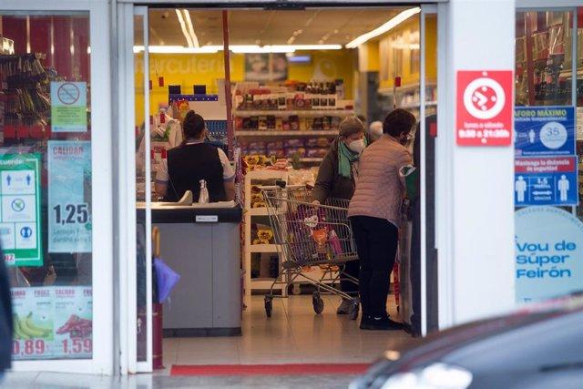 Archivo - Varias personas compran en un supermercado de Castro Riberas de Lea, perteneciente a la comarca de A Terra Cha, al no poder entrar en la ciudad de Lugo para comprar, en Outeiro de Rei, Galicia (España)