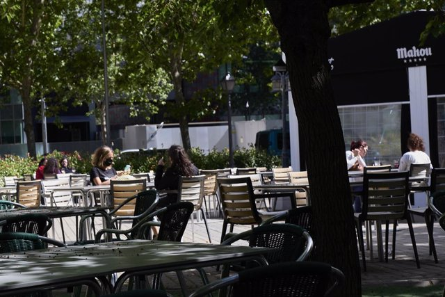 Varias personas en una terraza, durante el último fin de semana antes del término del uso de la mascarilla, a 20 de junio de 2021, en Madrid (España). Las mascarillas dejarán de ser obligatorias en los espacios al aire libre a partir del próximo 26 de jun