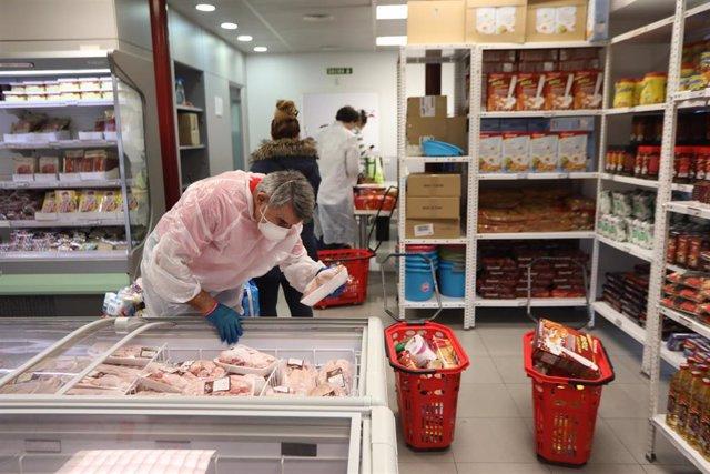 Archivo - Un voluntario manipula los alimentos de un refrigerador en el interior del economato solidario de Cáritas en Madrid.