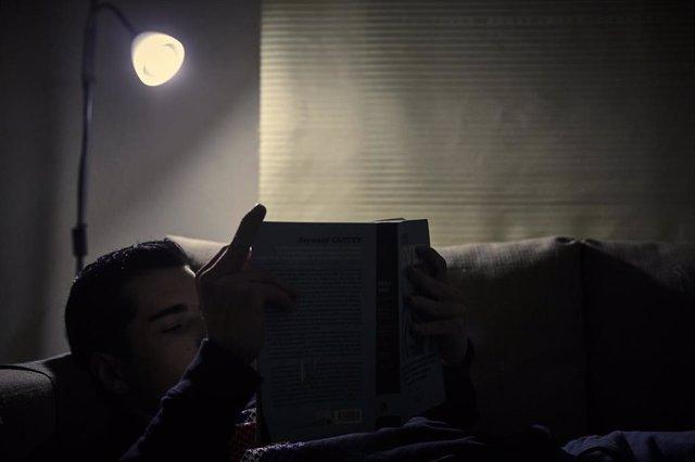 Archivo - Un chico lee un libro bajo la luz de una lámpara