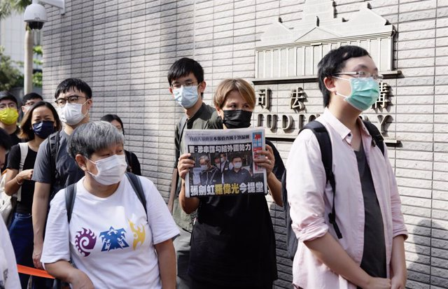 19 June 2021, China, Hongkong: People queue up outside Kowloon West Magistracy to attend audit while a supporter of Apple Daily displaying this morning's copy of Apple Daily's front cover depicting the political trial of the newspaper's executives, publis