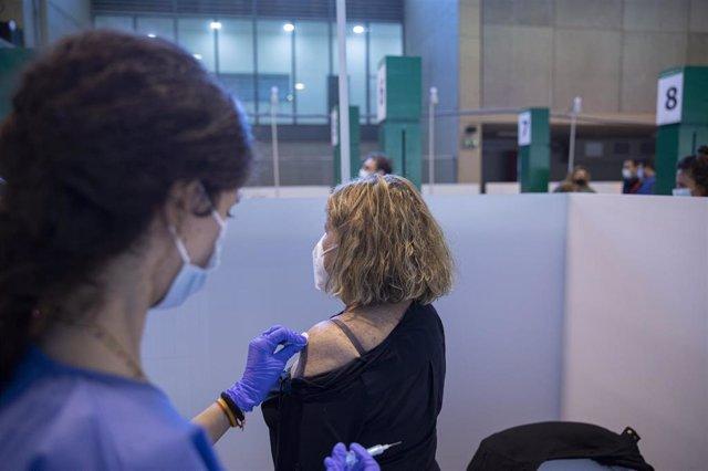 Archivo - Una sanitaria vacuna a una mujer.