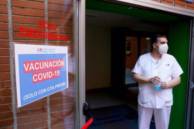 Un empleat sanitari al costat d'un senyal del dispositiu de vacunació engegat per a inocular la primera dosi de la vacuna de Pfizer-BioNTech contra el Covid-19, a 9 de juny de 2021, en l'Hospital Sever Ochoa de Leganés, Madrid, (Espanya).