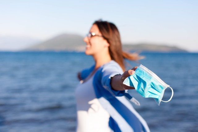 Archivo - Mujer en la playa con la mascarilla en la mano.