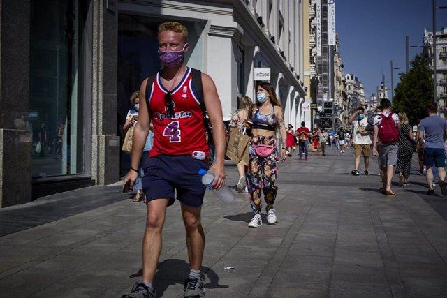 Un hombre camina por la Gran Vía de Madrid en un día de calor