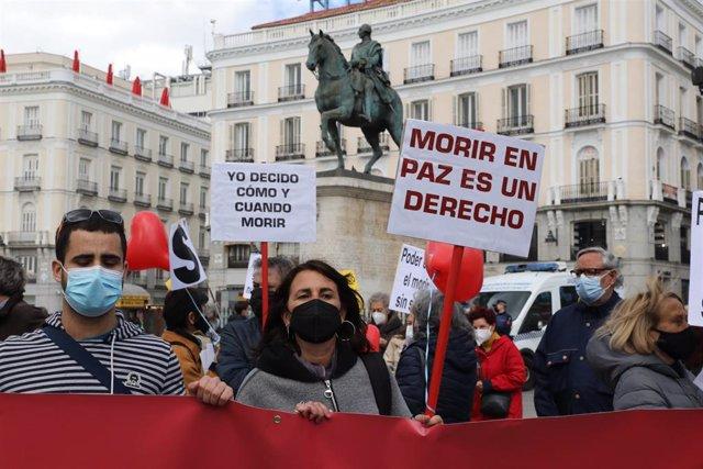 Archivo - Una mujer con un cartel en el que se lee: `Morir en paz es un derecho durante una concentración de Derecho a Morir Dignamente en la Puerta del Sol, en Madrid (España), a 18 de marzo de 2021. Derecho a Morir Dignamente se manifiesta para dar apo