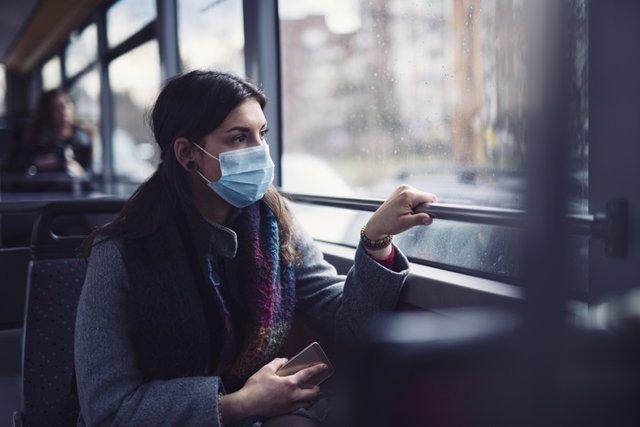 Archivo - Mujer con mascarilla en un autobús.