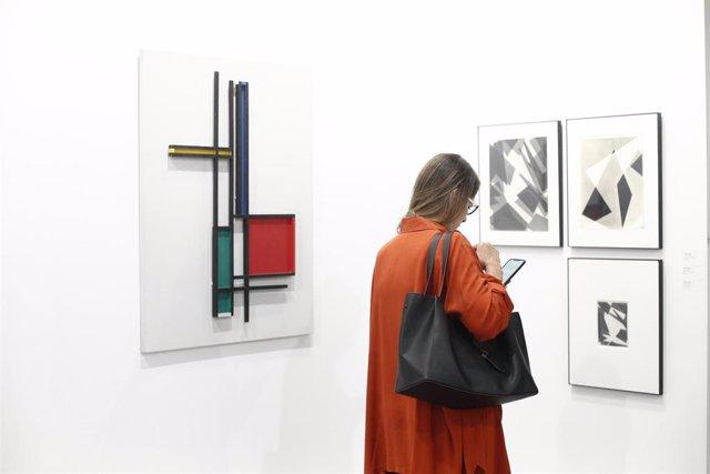 Archivo - Una mujer mira su móvil durante la pasada edición de ARCOmadrid.