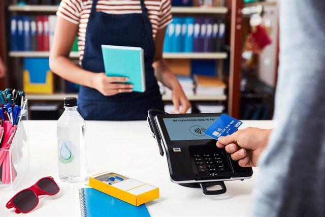 Archivo - Un cliente paga con tarjeta Visa en un comercio
