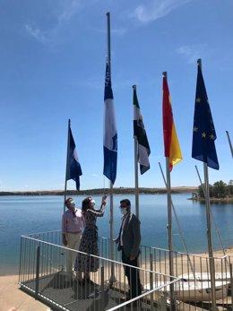 La consejera Nuria Flores iza una bandera en la playa de Orellana.