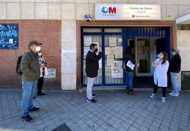 Archivo - Una trabajadora habla con un hombre delante del Centro de Salud Villaamil, delante del cual varias personas esperan a ser atenidas, en el distrito de Tetúan, en Madrid (España), a 26 de octubre de 2020. Infanta Mercedes y Villaamil (Tetuán)
