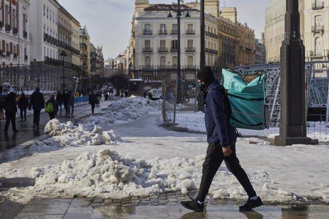 Archivo - Un empleado de Deliveroo camina con su mochila de reparto por la Puerta del Sol nevada tras restablecer parcialmente el servicio, en Madrid, (España), a 15 de enero de 2021. El paso de la borrasca 'Filomena' provocó una gran nevada por lo que la