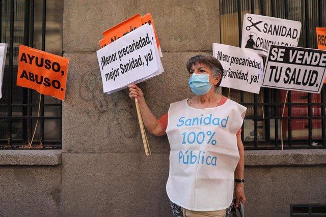 Una mujer vistiendo una camiseta representativa de la protesta y levantando pancartas, durante una concentración frente a la Consejería de Sanidad.