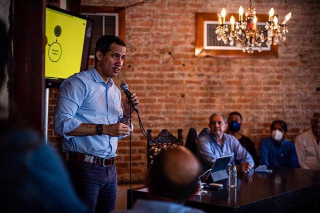 Archivo - 05 March 2021, Venezuela, Valencia: Venezuelan opposition leader Juan Guaido (L)speaks during a meeting with leaders of the Frente Amplio Venezuela Libre (FAVL) of Carabobo, a Venezuelan political organization, to coordinate efforts in the figh