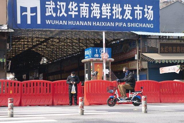Archivo - Dos ciudadanos pasan por la entrada del mercado de mariscos Huanan en Wuhan, provincia de Hubei, en el centro de China, el 29 de enero.