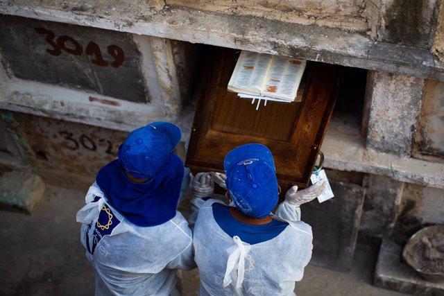 Archivo - Los trabajadores del cementerio entierran a una  víctima del coronavirus en el cementerio de Caju el 24 de marzo de 2021 en Río de Janeiro, Brasil.