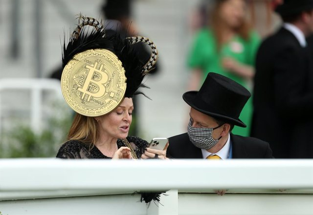 19 June 2021, United Kingdom, Ascot: A racegoer wears a hat with a large Bitcoin symbol on day five of Royal Ascot at Ascot Racecourse. Photo: Steven Paston/PA Wire/dpa