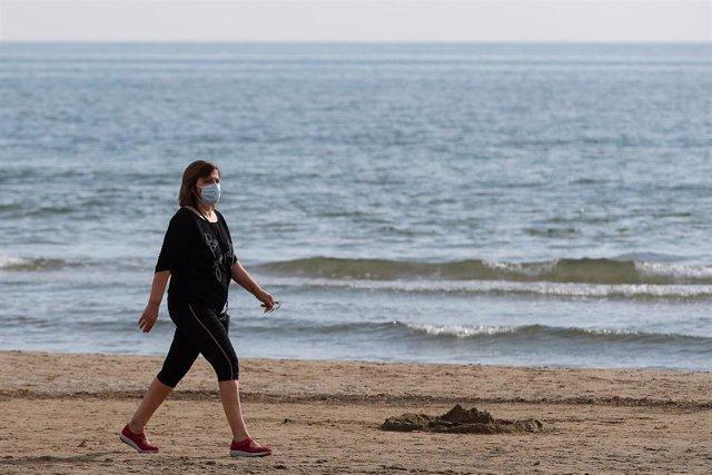 Archivo - Una mujer con mascarilla pasea por la playa de la Malvarrosa
