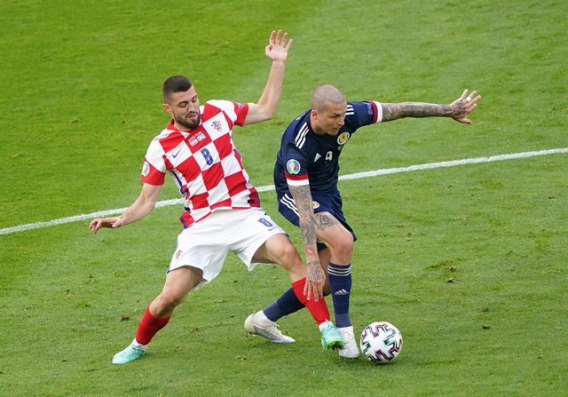 22 June 2021, United Kingdom, Glasgow: Croatia's Mateo Kovacic (L) and Scotland's Lyndon Dykes battle for the ball during the UEFA EURO 2020 Group D soccer match between Croatia and Scotland at Hampden Park. Photo: Owen Humphreys/PA Wire/dpa