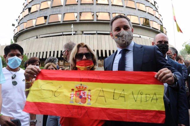 El presidente de Vox, Santiago Abascal, y una mujer sostienen una bandera de España contra la ley de eutanasia, en el Tribunal Constitucional, a 16 de junio de 2021, en Madrid (España).