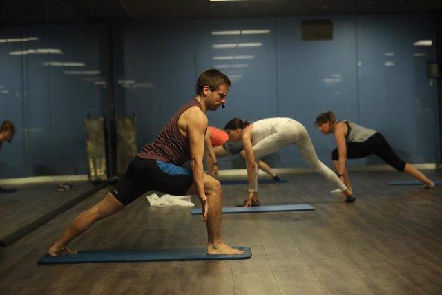 Archivo - Un entrenador imparte clase a varias personas en una clase de Body Balance en un gimnasio de Madrid.