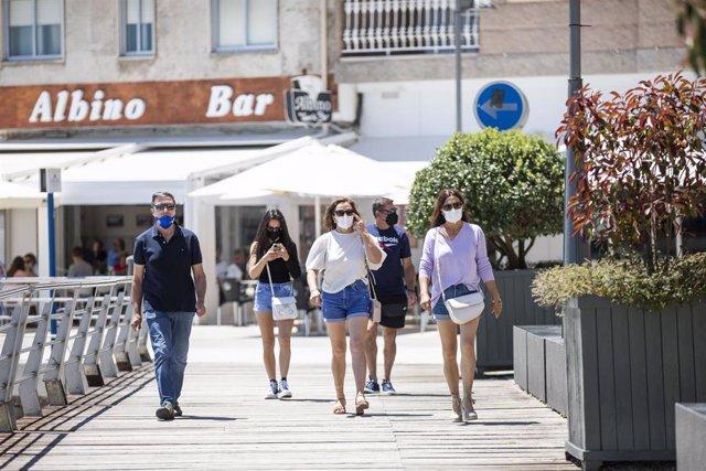 Varias personas en el paseo marítimo de la playa de Sanxenxo, a 4 de junio de 2021, en Sanxenxo, Pontevedra, Galicia, (España). El aumento de las temperaturas y la progresiva mejora de la situación epidemiológica ha colaborado en que los gallegos comience