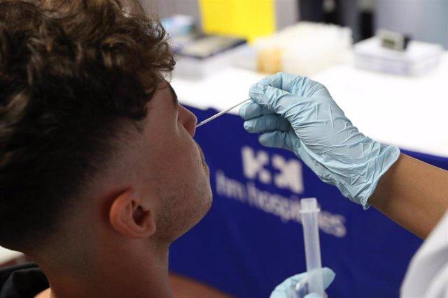 Un sanitario realiza un test de antígenos a un hombre.