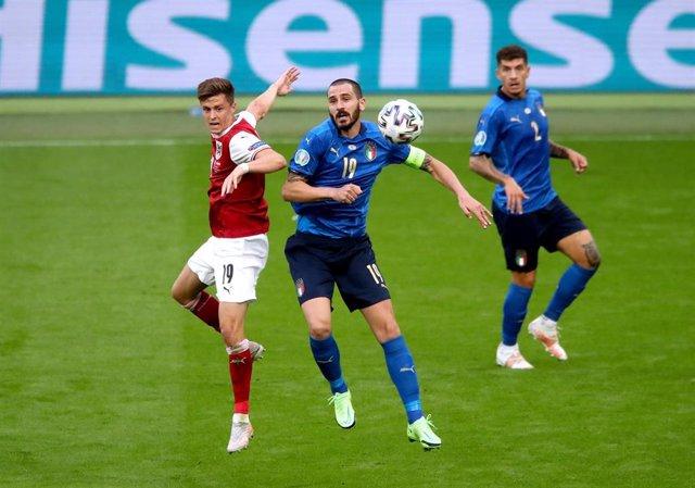 Christoph Baumgartner y Leonardo Bonucci pelean por un balón en el Italia-Austria
