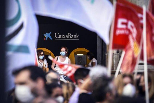 Un grupo de empleados de CaixaBank protesta contra la entidad financiera por el ERE previsto para miles de empleados, a 22 de junio de 2021, en Valencia, Comunidad Valenciana, (España).