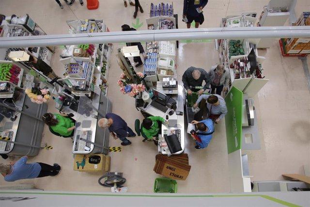 Archivo - Varias personas compran en el interior de una gran superficie