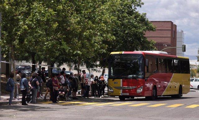 Una fila de pasajeros espera para subirse a un autobús
