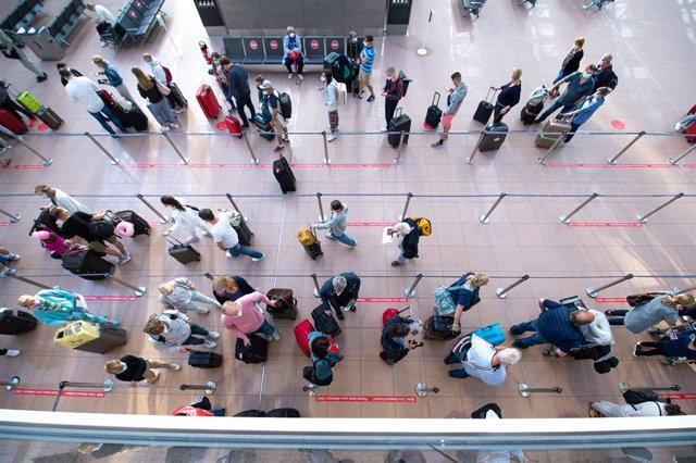 25 June 2021, Hamburg: Passengers wait in queues in front of check-in desks in Terminal 1 at Hamburg Airport. Around 100 take-offs and landings are planned for Friday, the airport announced. Around 20,000 passengers are expected to arrive or depart. Photo