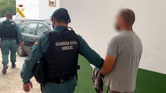 Un agente de la Guardia Civil conduce a un detenido en una operación contra el tráfico de droga en la provincia
