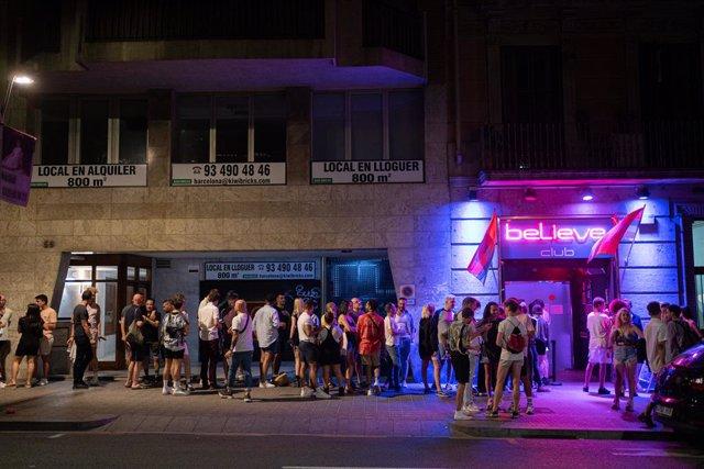 Arxiu - Un grup de joves fa cua per entrar a una discoteca