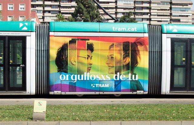 Un tramvia amb la imatge de la bandera LGTBI amb el lema 'orgullosxs de tu'.