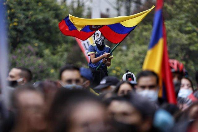 Archivo - Un niño enmascarado agita una bandera colombiana durante una protesta contra el gobierno del presidente Iván Duque.