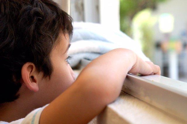Archivo - Niño mirando por la ventana.