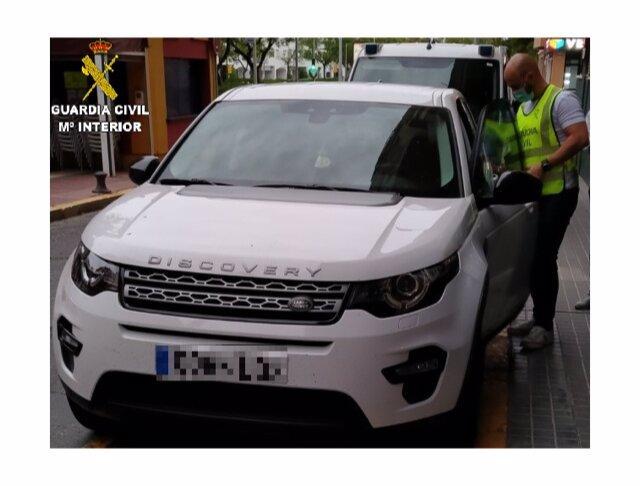 Agente de la Guardia Civil en Huelva junto al vehículo que fue objeto de estafa.