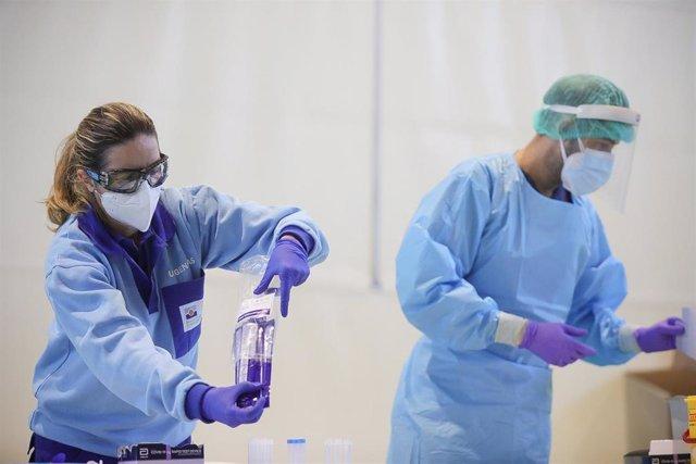 Archivo - Profesionales sanitarios realizan test de detección de Covid