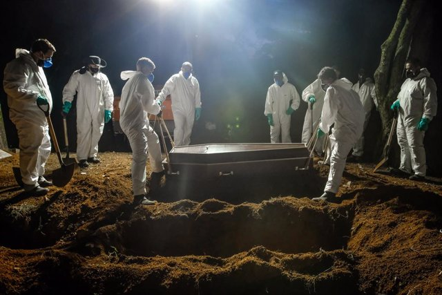 Archivo - FILED - 02 April 2021, Brazil, Sao Paulo: Employees of the Vila Formosa cemetery, the largest in Latin America, carry a coffin to bury a person who died of coronavirus (Covid-19). Due to the high number of deaths, the employees also work during