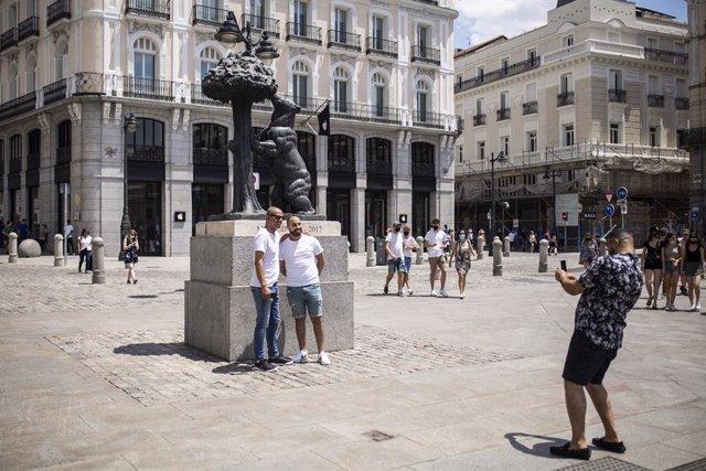 Un hombre toma una foto a otros dos, sin mascarilla en la Puerta del Sol, durante el primer día en el que no es obligado el uso de la mascarilla en exteriores desde el inicio de la pandemia, a 26 de junio de 2021, en Madrid (España). El 30 de marzo de 202