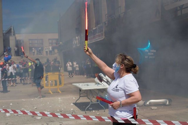 """Una mujer sostiene una bengala durante una concentración en conmemoración del año de """"lucha"""" por la planta de aluminio y los puestos de trabajo de Alcoa San Cervo, en la Praza do Concello de Xove, a 30 de mayo de 2021, en Xove, Lugo, Galicia (España)."""