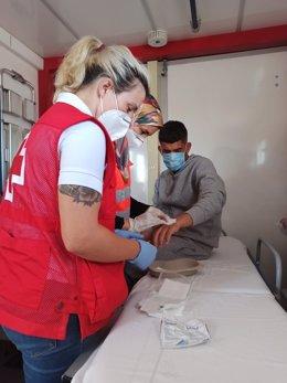 Personal de Cruz Roja atiende a una persona migrante llegada a Calp este lunes en patera