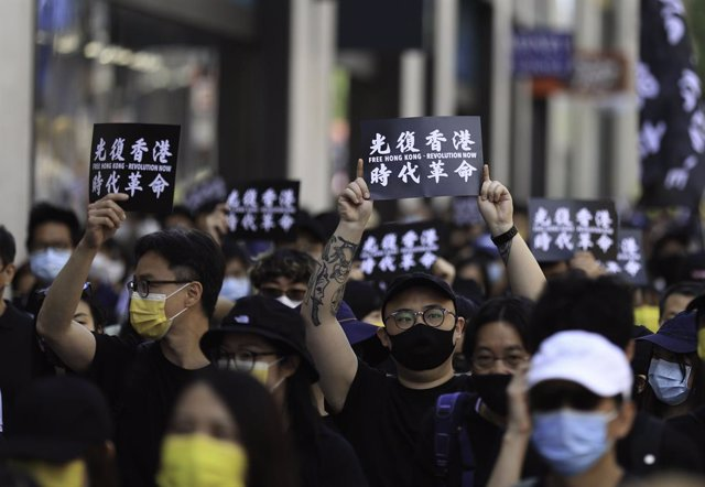 """12 June 2021, United Kingdom, London: Pro-democracy activists hold placards that read """"liberate Hong Kong, revolution of our times"""" during a rally marking the second anniversary of the start of massive pro-democracy protests which roiled Hong Kong in 2019"""