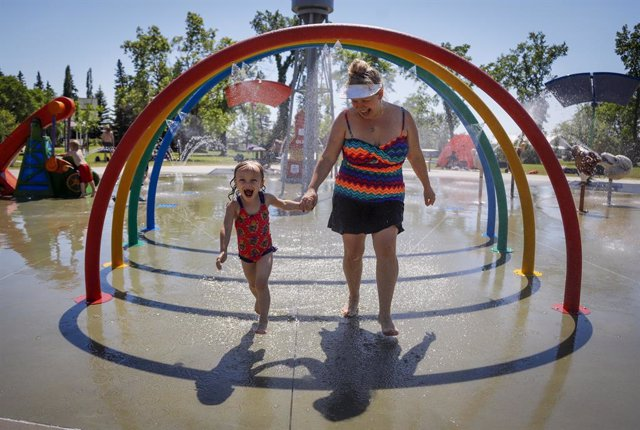 28 June 2021, Canada, Olds: Poppy Collins (L), five, and her mother Crystal Collins run through spray to try and beat the heat at a splash park. Environment Canada warns the torrid heat wave that has settled over much of Western Canada won't lift for days
